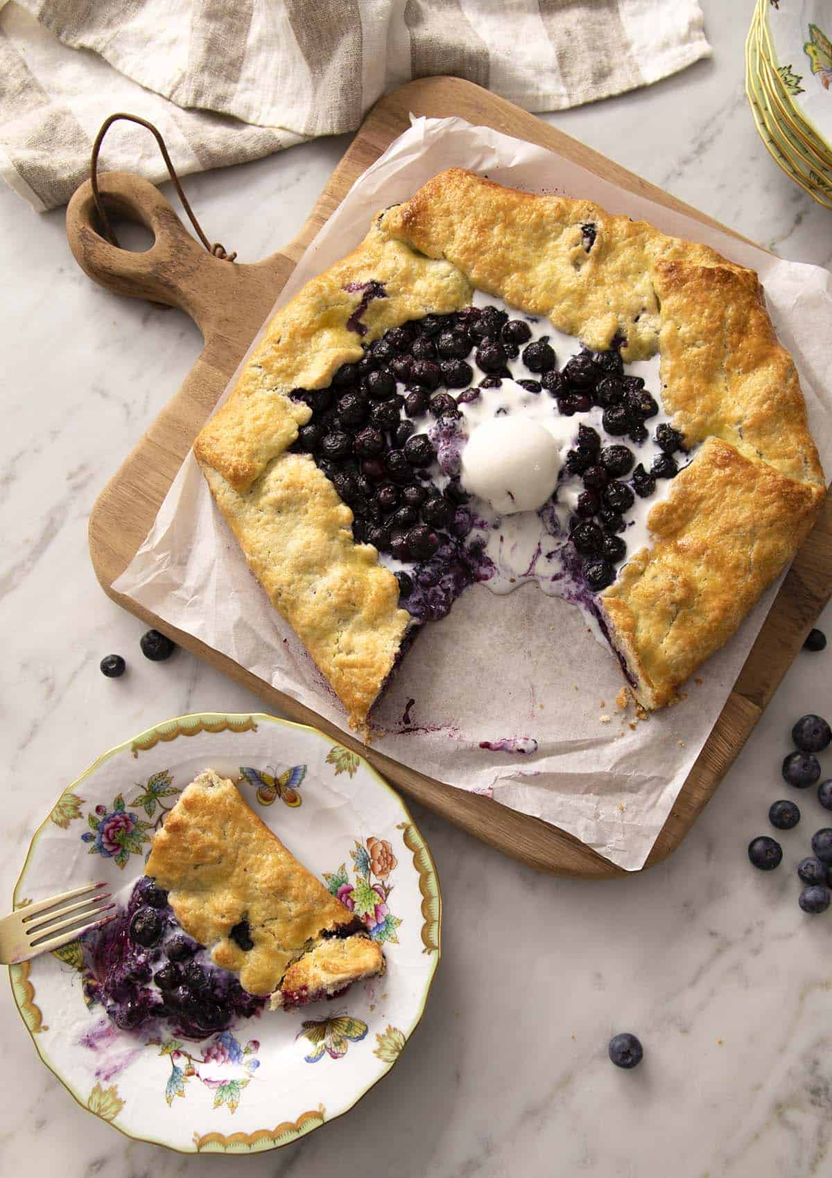 A blueberry galette with a piece removed and on a plate.
