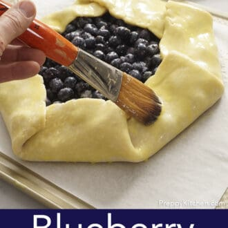 A blueberry galette getting brushed with an egg wash.