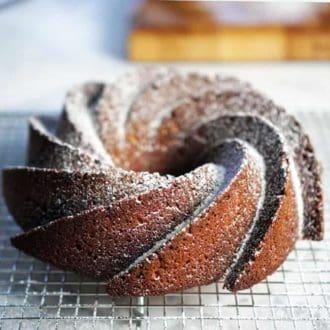 A vanilla bundt cake covered with powdered sugar on a cooling rack