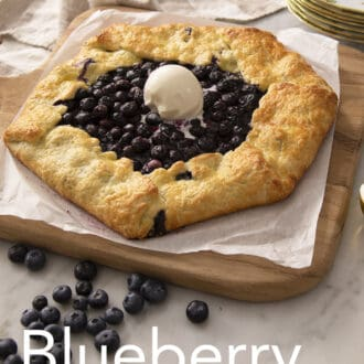 A blueberry galette on a wooden board next to an ice cream scoop.