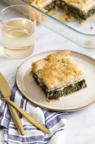 A photo of a piece of spanakiopita on a white marble table with a glass of white wine.