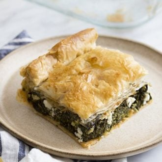 A close up photo of Spanakopita on a tan plate