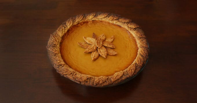 A photo of a pumpkin pie with leaves made from pie crust decorated on the middle of the cake