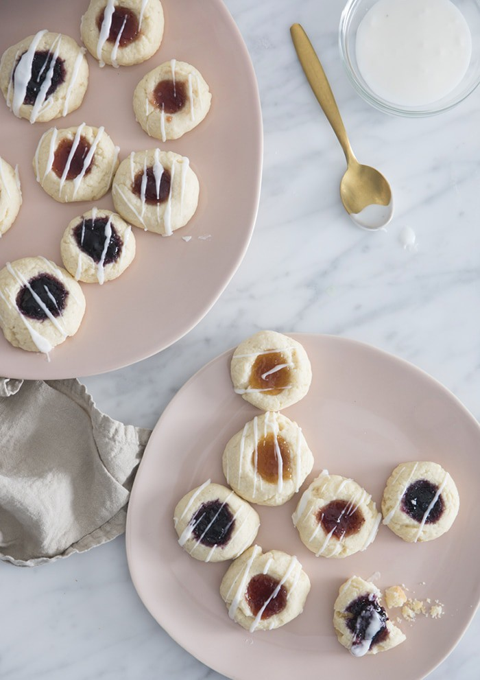 A photo of a group of thumbprint cookies on pink plates.