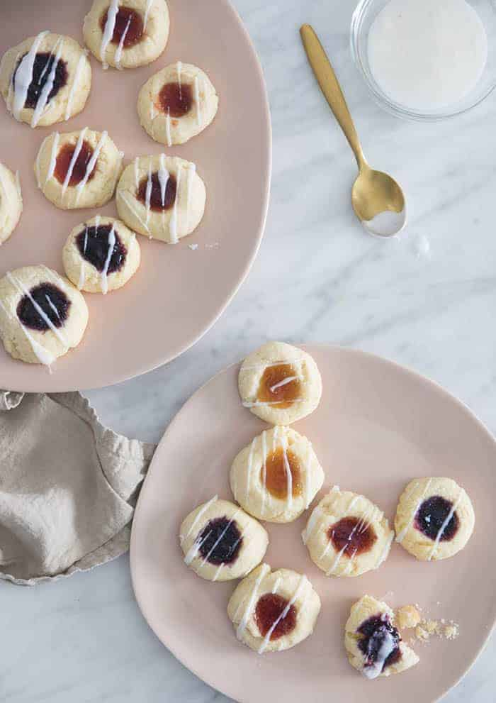Two soft pink plates filled with thumbprint cookies on a white marble table