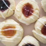 thumbprint cookies with different jams in the middle on a soft pink plate