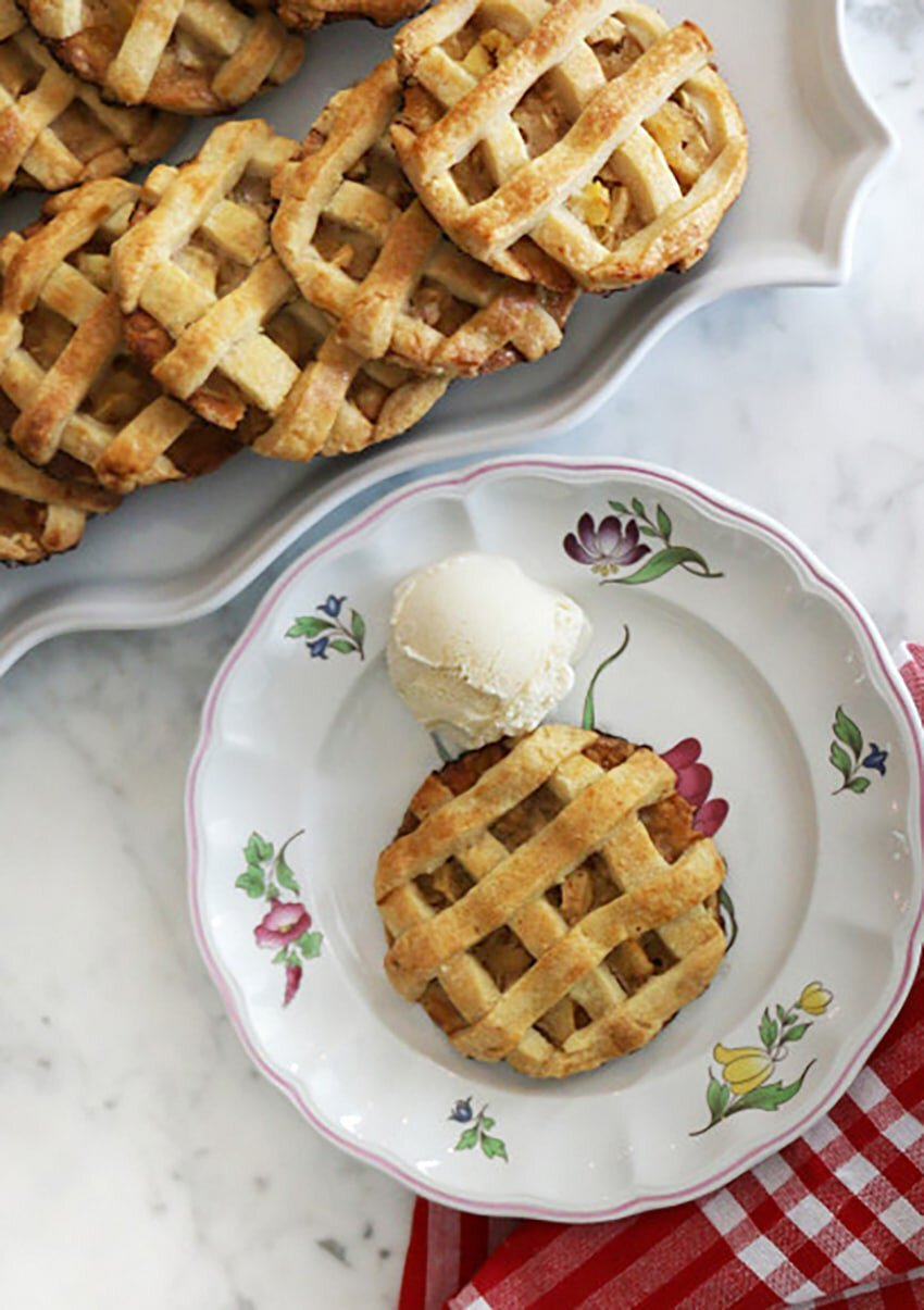 A mini apple pie on a plate with a scoop of vanilla ice cream.