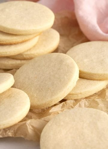 Round sugar cookies on a crinkled piece of parchment paper