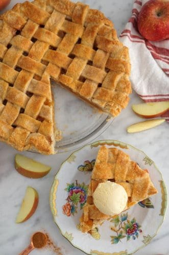 A top town photo of an apple pie with a lattice top and a piece on a plate.