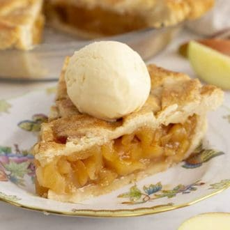 A piece of apple pie topped with a scoop of vanilla ice cream