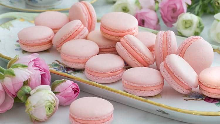 A group of pink French macarons on a rectangilar porcelain place with flowers