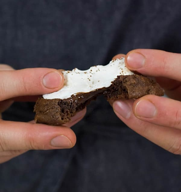 A photo showing chocolate cookies topped a melted marshmallow being pulled apart