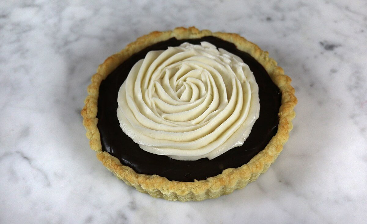 A photo of a chocolate tart topped with a spiral of buttercream.