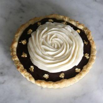 Chocolate Tart with gold flecks on marble.