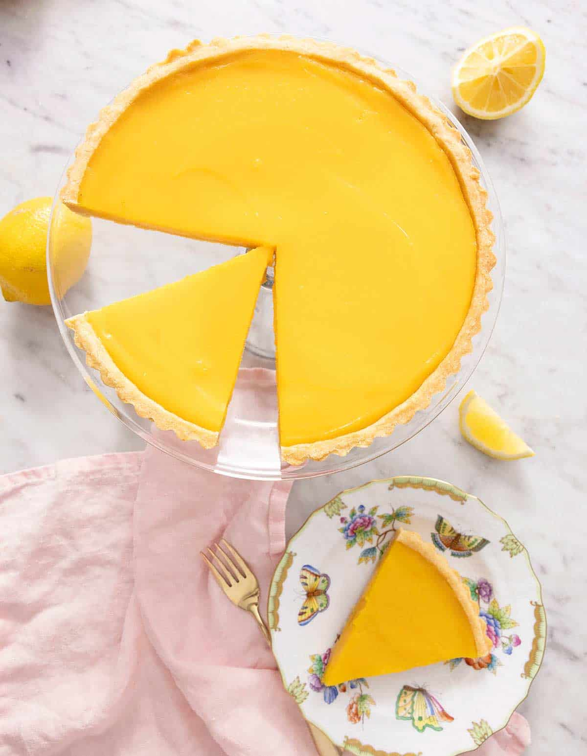 An overhead shot of a lemon tart on a cake stand and a slice on a plate