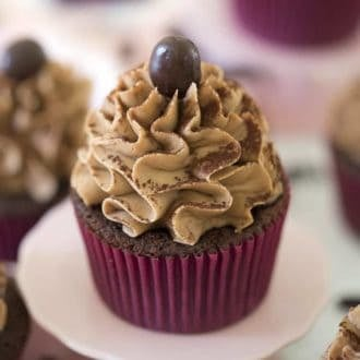 A chocolate cupcake on a pin stand topped with a ruffled dollop of mocha buttercream