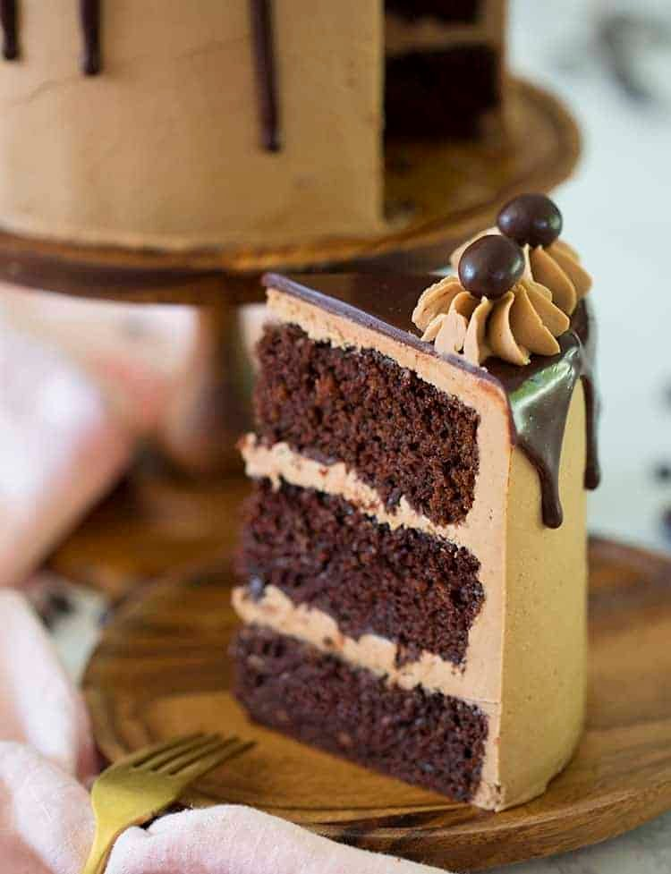 A slice of mocha cake with a ganache drip on a wooden plate