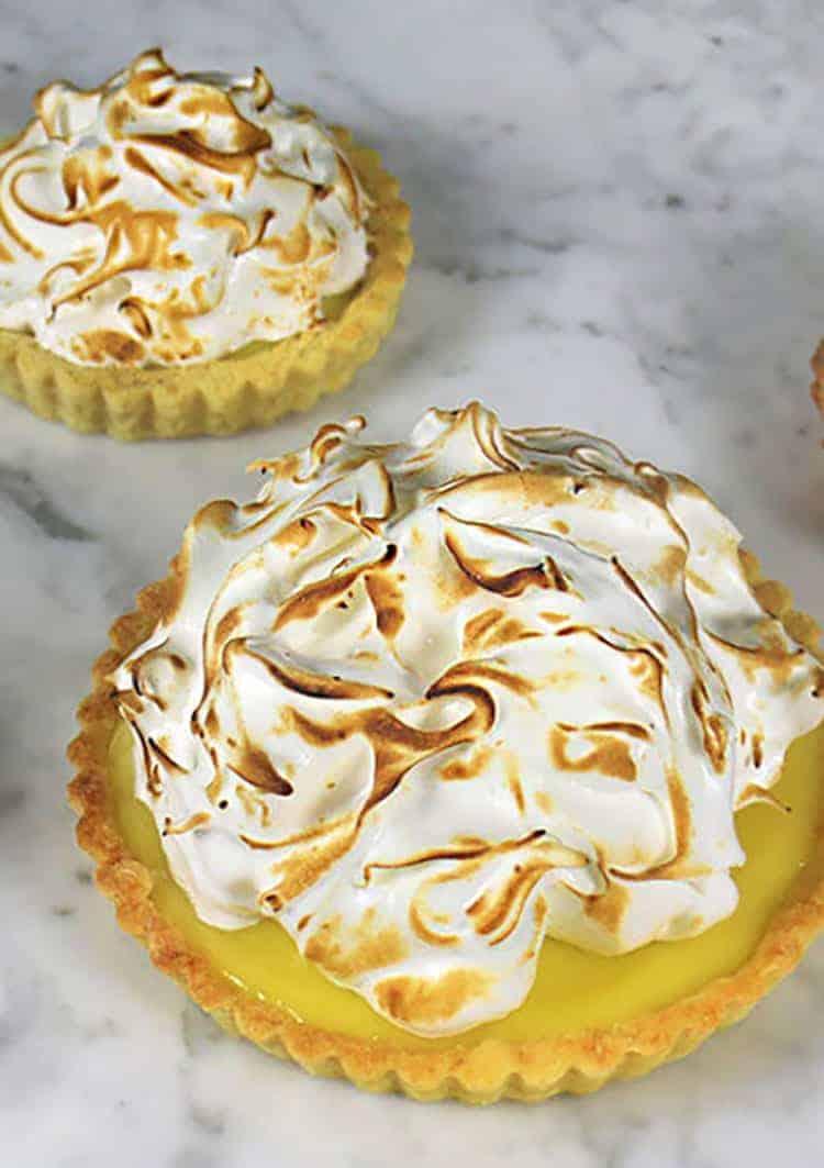 lemon meringue tarts on a white marble table