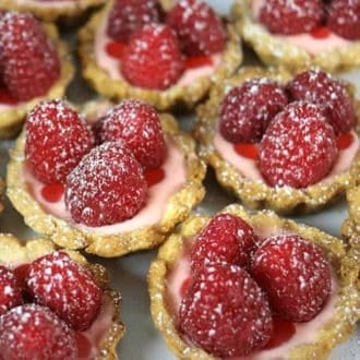 Little raspberry tarts topped with three raspberries each
