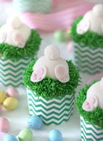 A photo of bunny butt cupcakes with chocolate eggs around them.