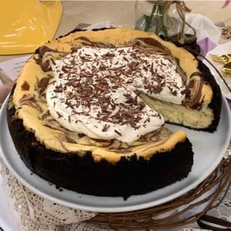 chocolate cheesecake with an Oreo crust topped with whipped cream and shaved chocolate