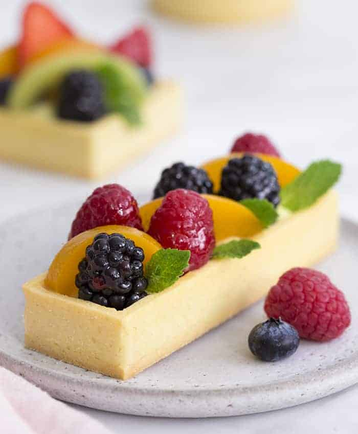 A photo showing a rectangular fruit tart on a gray plate.