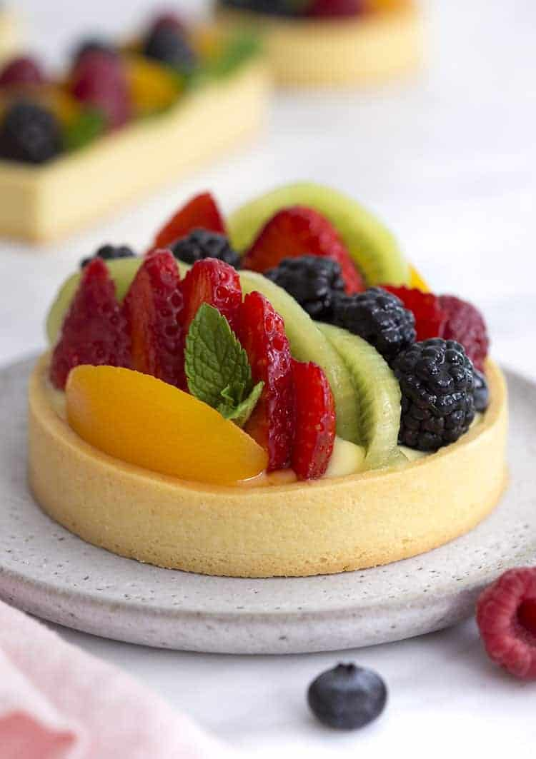 A photo of a fruit tart with various berries, peach slices and kiwis.