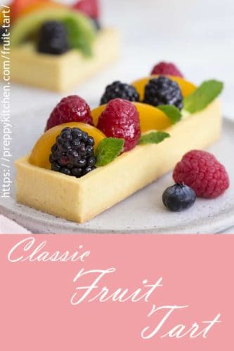 a photo of a rectangular fruit tart with a few sprigs of mint.