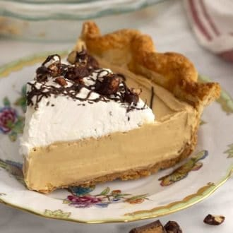 a piece of peanut butter pie topped with whipped cream and chocolate
