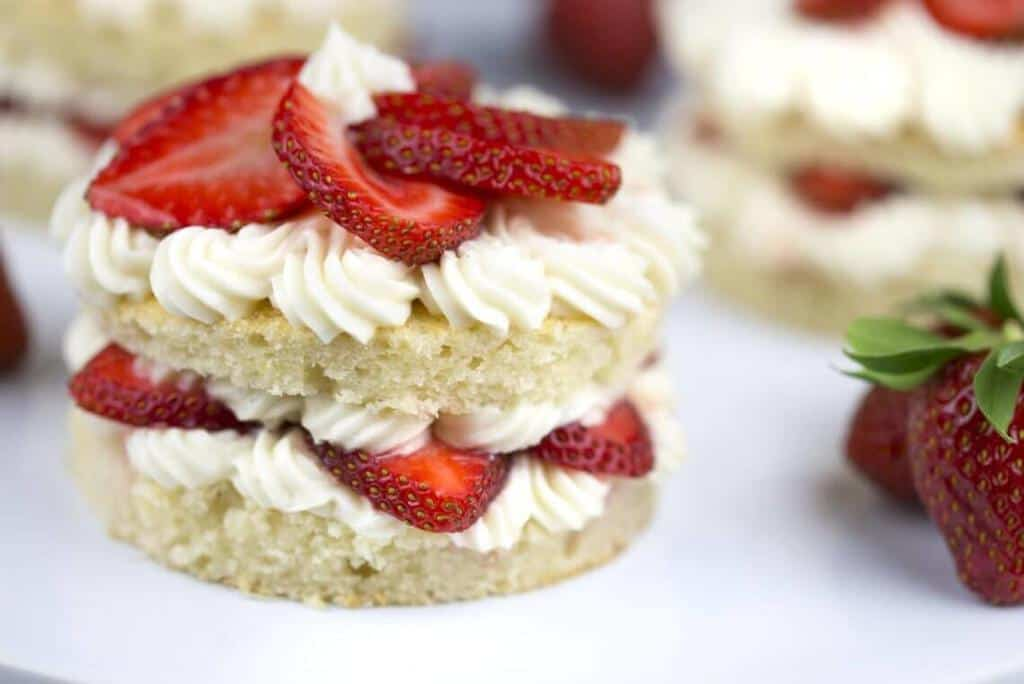 A Strawberry Layer Cake with fresh strawberries on top.