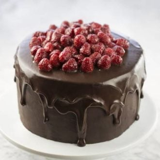 a chocolate raspberry cake on a white cake stand