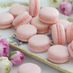Pink french macarons on a painted porcelain plate with flowers