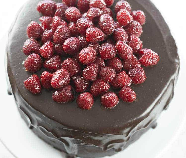 A large chocolate cake covered in raspberries