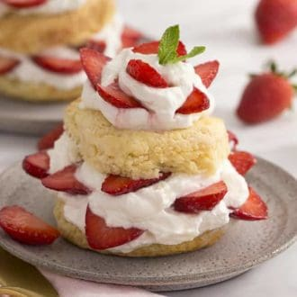 A strawberry shortcake on a grey plate covered in strawberries