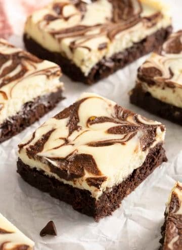 Cheesecake brownies with a chocolate swirl on parchment paper.