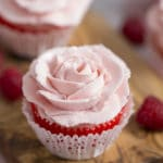A closeup photo of a cupcake with a soft pink rose piped on top
