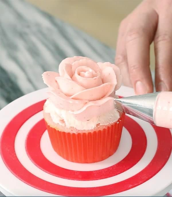 A photo showing a pink buttercream rose being piped onto a pink cupcake.