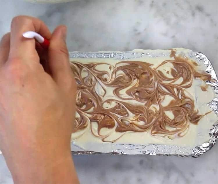 Chocolate being swirled into a cheesecake bar