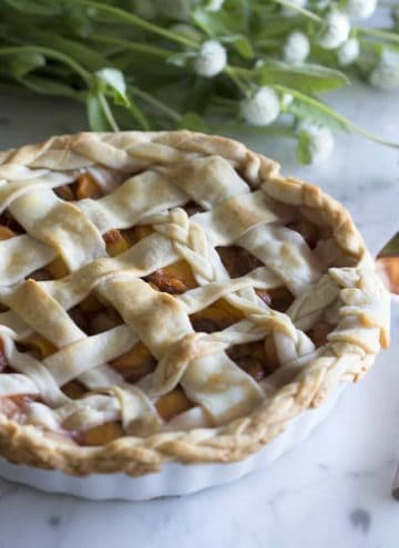 A peach and cherry pie next to white flowers