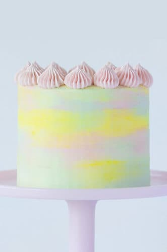 A pastel watercolor cake on a pink cake stand