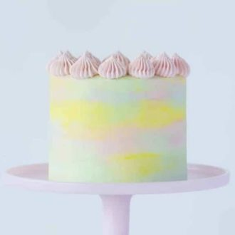 A photo of a beautiful Watercolor Cake on a cake stand.