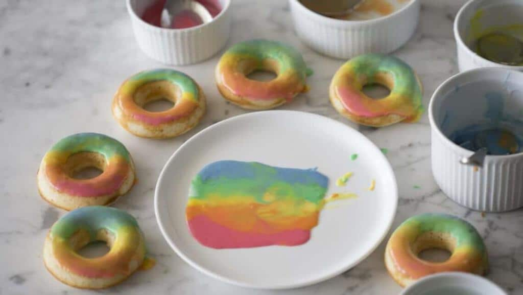 A photo of rainbow donuts and the ingredients to make them.