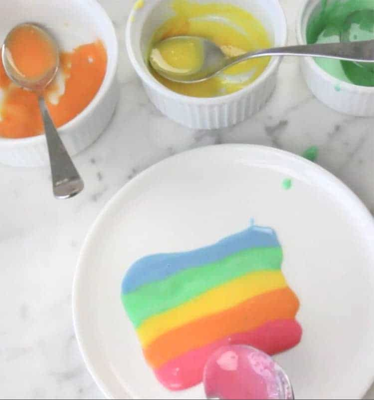 Different colored glazes lined up in a rainbow on a plate