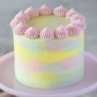 A pastel pink, blue and yellow watercolor cake on a pink cake stand.