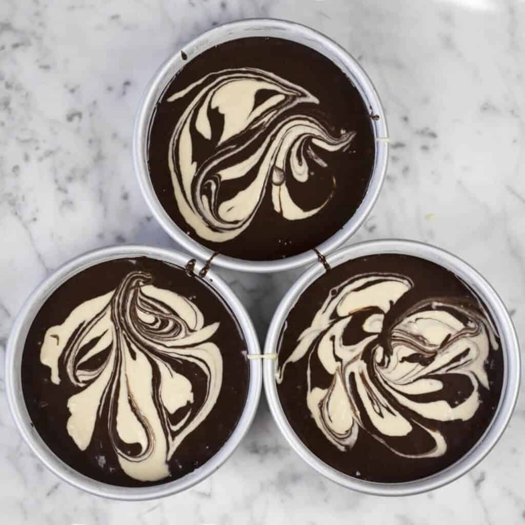 a photo of three pans filled with chocolate peanut butter cake batter.