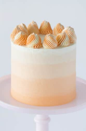 a photo showing a creamsicle cake with swirled orange and white dollops on top.