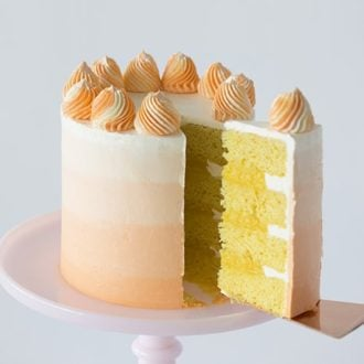 A photo of an orange ombré cake on a pink cake stand