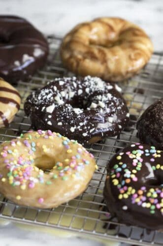 A photo of Chocolate Eclair Donuts on a cooling rack.
