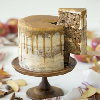 Photo of an apple spice cake with caramel on a wooden cake stand