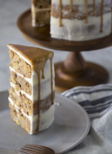 A piece of apple spice cake on a plate with the rest of the cake behind it.